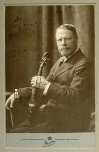 Hugo Heermann (1844-1935), der Initiator der deutschen Erstaufführung des Sextetts. Undatierte Portraitphotographie aus dem Studio von Arthur Marx, mit Notenzitat (Incipit der Solostimme von Beethovens Violinkonzert) und verblaßter Widmung an den amerikanischen Geiger Henry C. Heyman (1855-1924).
